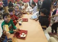2nd and 4th graders making Gingerbread Houses